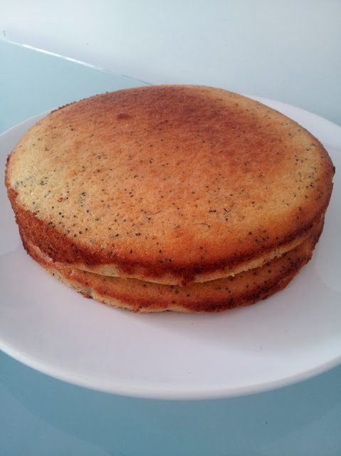 gluten free lemon and poppy seed large cake on a white round plate on a blue glass table top